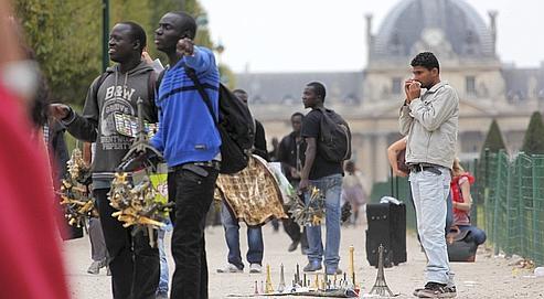 Des vendeurs à la sauvette de mini Tour Eiffel ou de souvenirs parisiens, sont en action dans les environs de la Tour Eiffel. Paris le 26/07/2011. Photo François Bouchon / Le Figaro